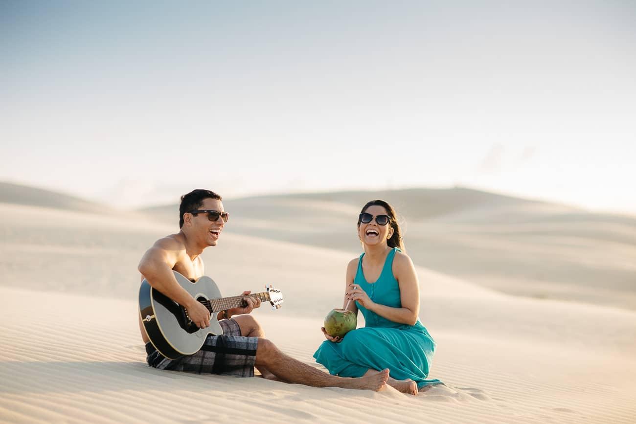 fotos de casal sorrindo na praia tocando violão e bebendo água de côco
