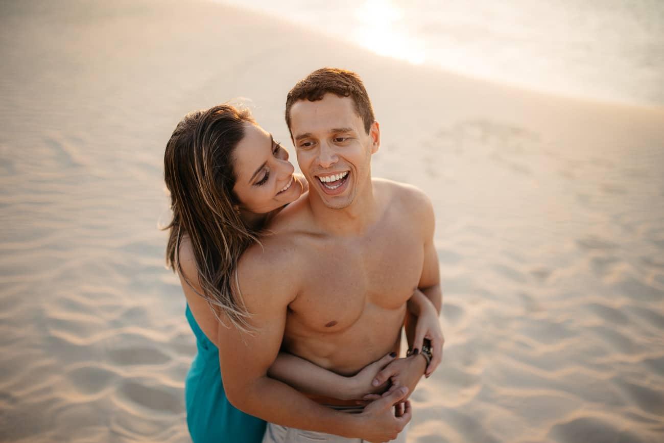 foto de casal sorrindo na duna sem camisa