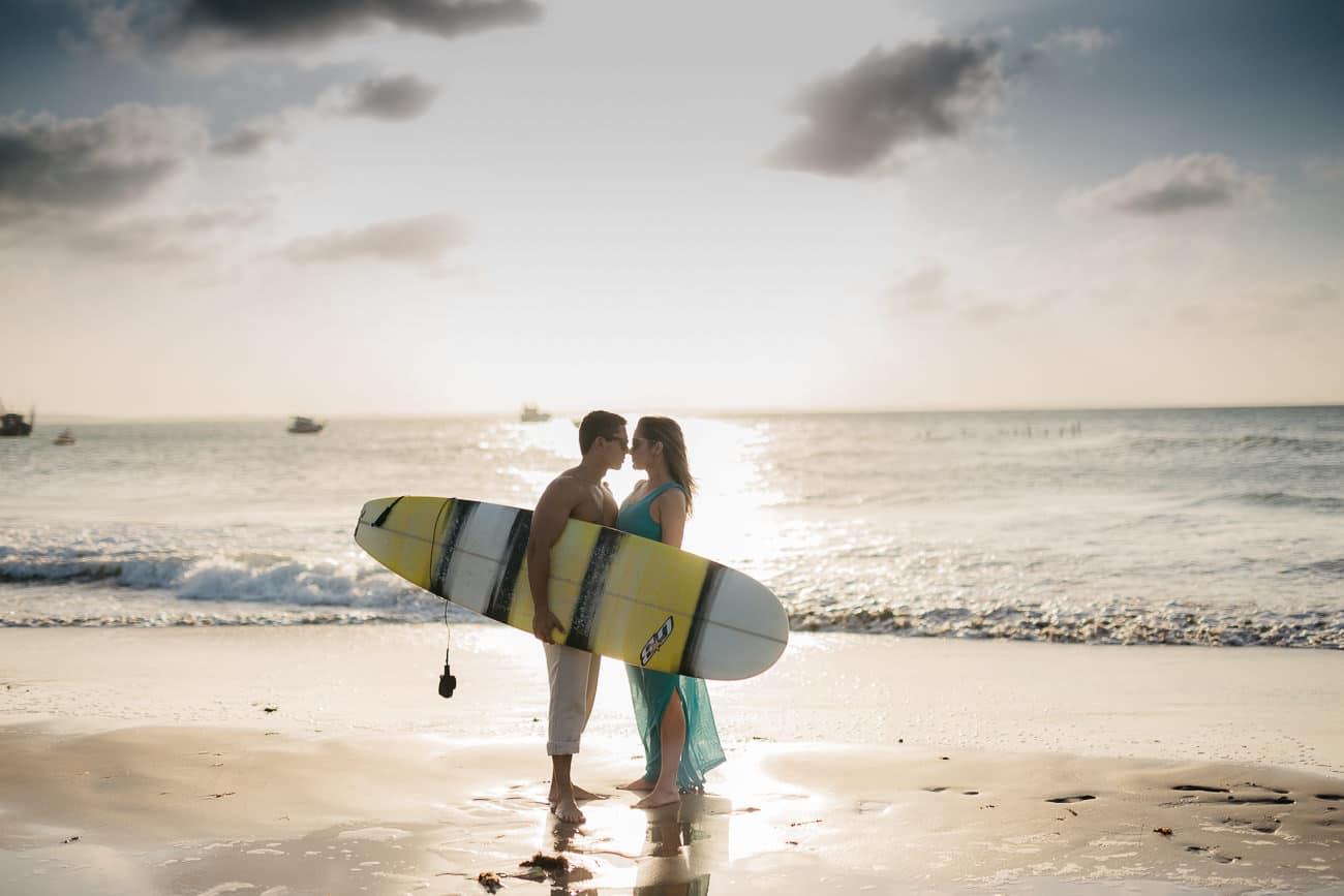 foto de casal na praia com prancha de surf