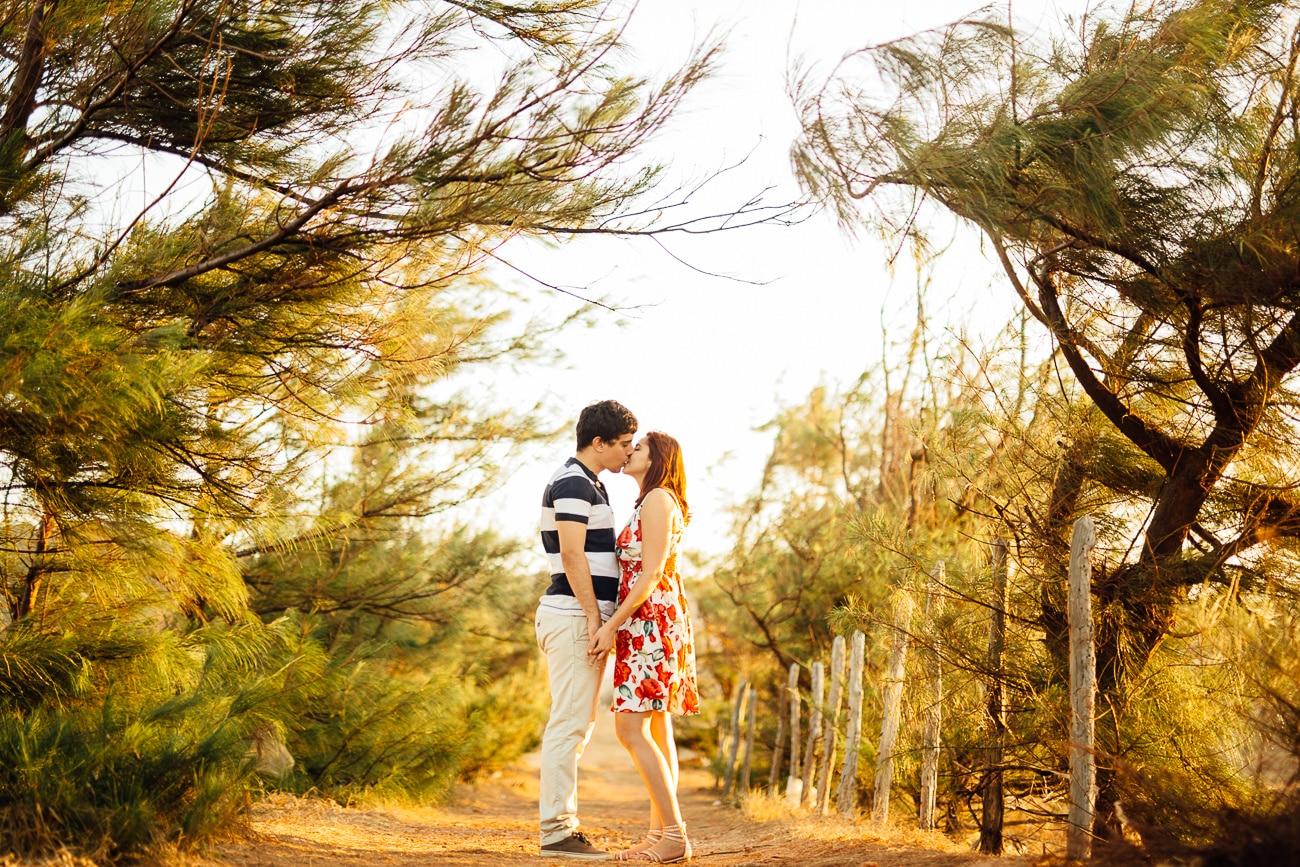 Fotos de casal em meio aos pinheiros com luz do por do sol.