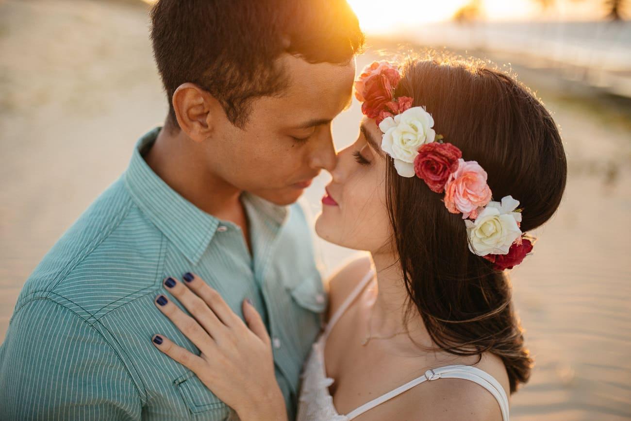 Fotografia de casal na praia ao por do sol