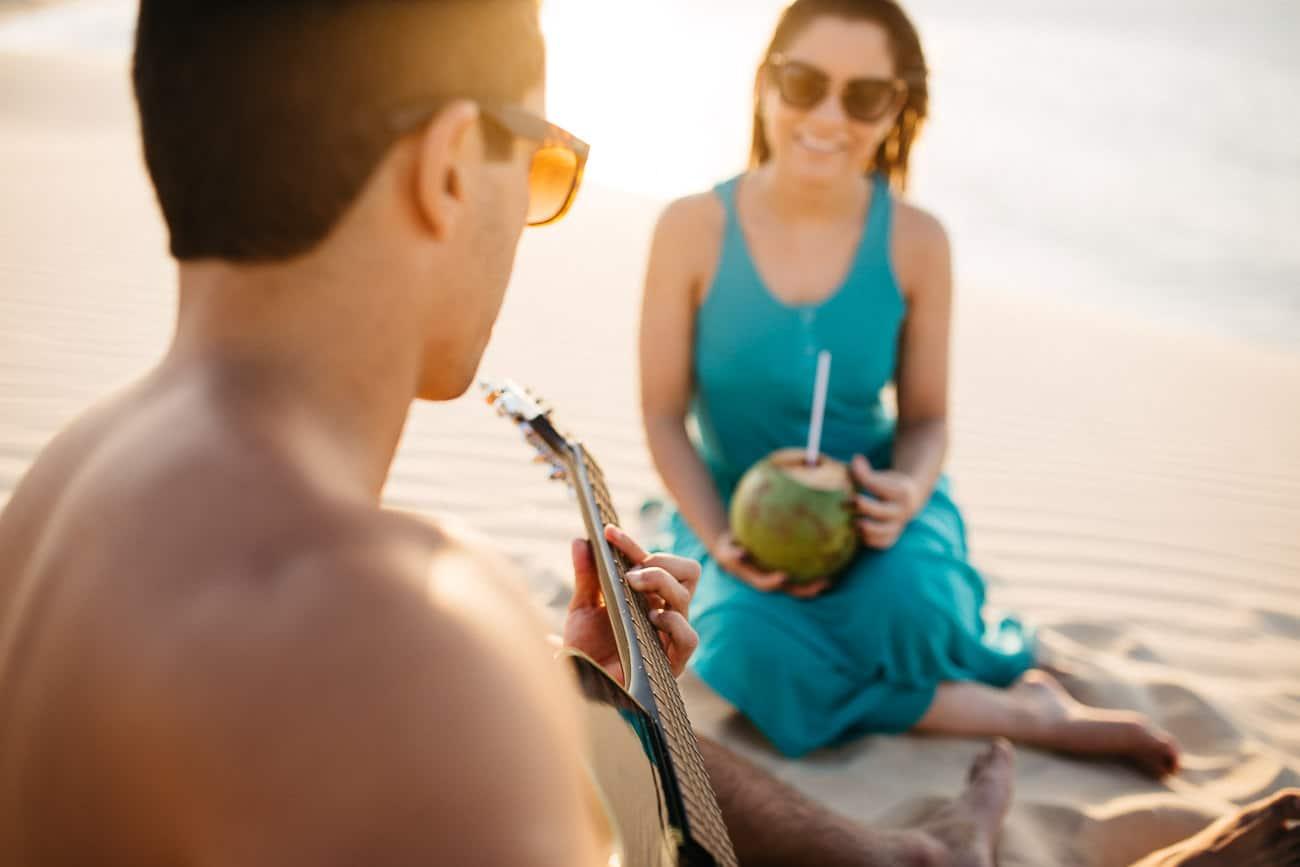 foto de casal tocando violão na praia