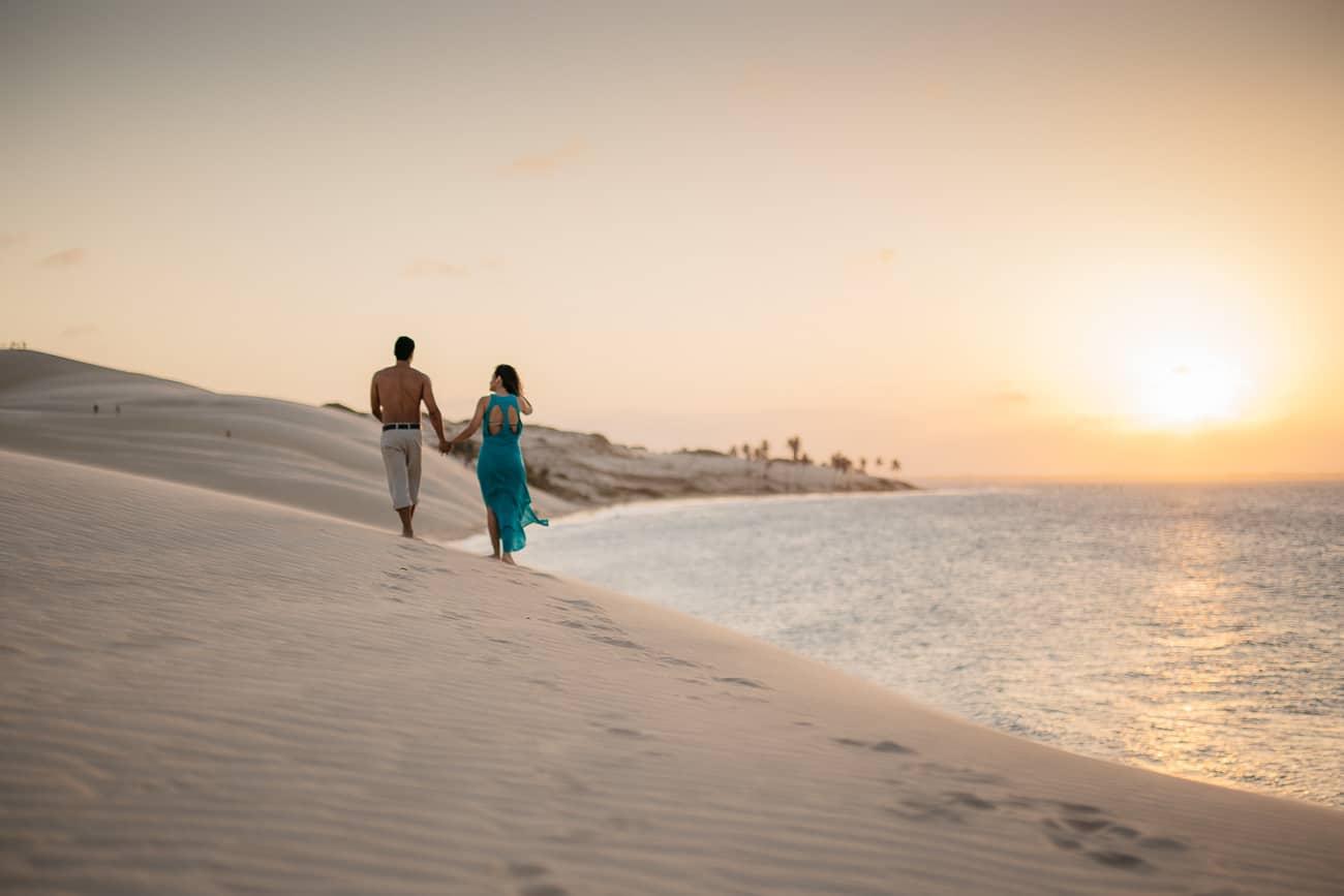 Foto de casal caminhando na duna ao por do sol