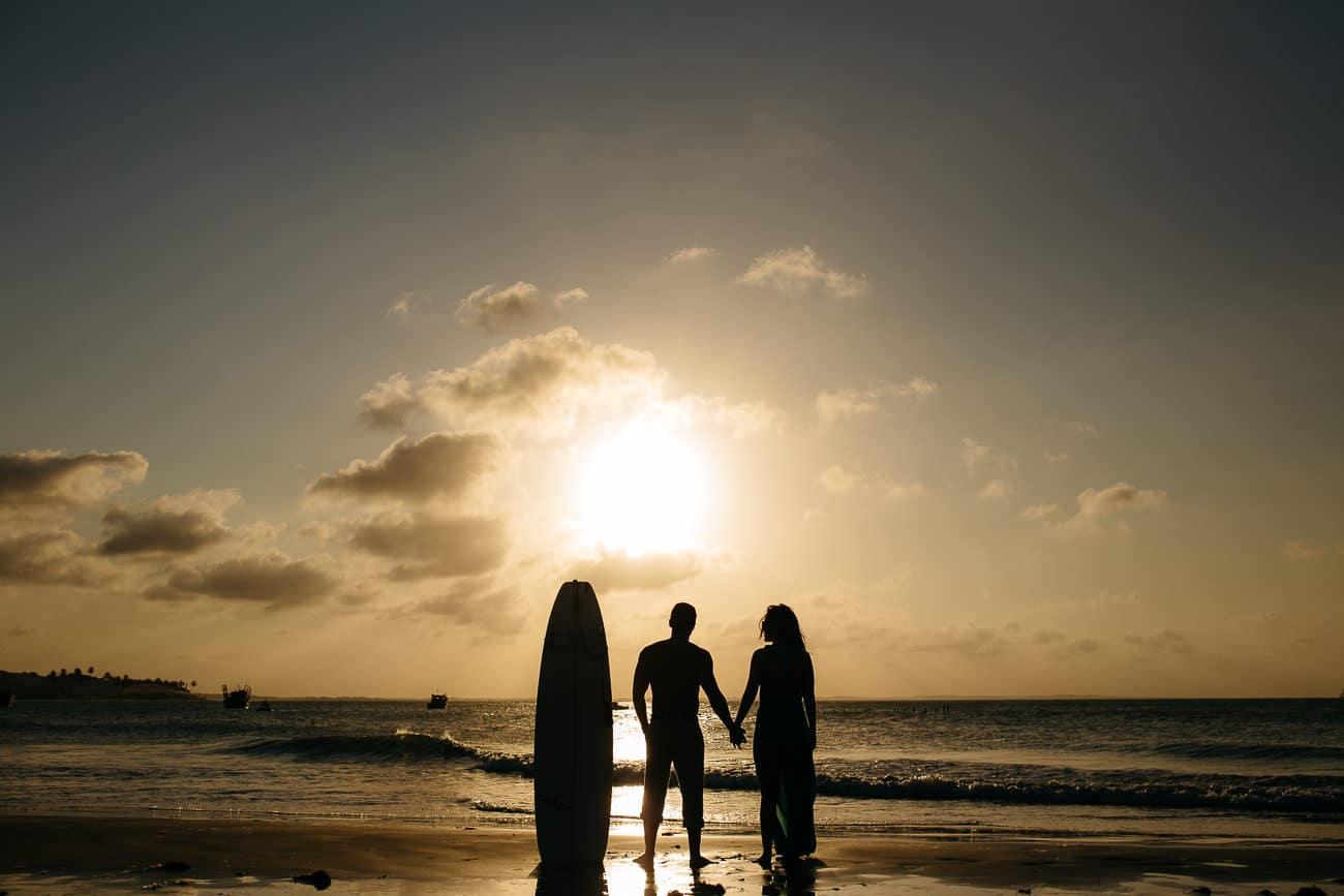 foto de casal surfista na praia ao por do sol